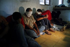 A group of people kidnapped by alleged drug-traffickers, sit on the floor after being rescued by members of the Mexican Army in Sabinas Hidalgo, 99 km north of Monterrey, Nuevo Leon State, Mexico, on April 27, 2010. Sixteen people, including a woman and a two-year girl, were rescued during the operation. AFP PHOTO/Dario Leon (Photo credit should read Dario Leon/AFP/Getty Images)