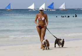 Sun lover walks her dogs on a beach in Boracay island in Malay town, province of Aklan, central Philippines.